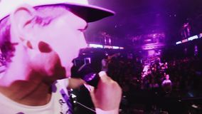 Mc man perform on stage with girl. People dancing on party in nightclub. Lights stock footage
