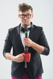 MC putting microphone into the cup Royalty Free Stock Photo