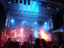 MC Yogi sings into mic as he preforms on stage with DJ Drez Stock Image