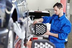 Mécanicien automobile au travail d'alignement des roues avec le capteur Photographie stock libre de droits