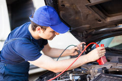 Mécanicien employant des câbles au démarrage un moteur de voiture Photographie stock libre de droits