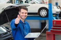 Mécanicien à l'aide de son ordinateur portable montrant des pouces  Images stock