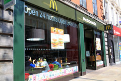 McDonald's. London, United Kingdom, Apr 17, 2011 : McDonald's fast food outlet in Kensington with its new green and yellow colours showing customers enjoying Stock Images