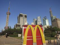 McDonalds in Shanghai: The McDonalds Logo in Front. The McDonalds logo in front of the Pudong skyline illustrates how business today is becoming globalized Stock Photography