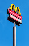 McDonald's logo on a pole against the blue sky Royalty Free Stock Photography