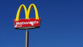 McDonald's sign against blue sky. A McDonald's sign early in the morning against a  blue sky. You can see the sun reflecting off the sign Royalty Free Stock Photo