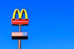 McDonaldsembleem tegen blauwe hemel met Mc Aandrijvingsinschrijving in Rus Royalty-vrije Stock Afbeelding