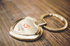 McHappy key holder. POZNAN, POLAND - JANUARY 24, 2017: Mc Donalds McHappy Day heart shaped metal key holder on wooden table in soft focus Stock Image