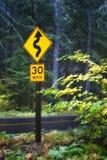 McKenzie通行证路标驾驶慢由于曲线 免版税库存图片