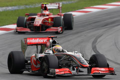 McLaren Mercedes F1 Team Lewis Hamilton 2009. McLaren Formula One driver Lewis Hamilton takes the corner ahead of Scuderia Ferrari Kimi Raikkonen at the Sepang Royalty Free Stock Photos
