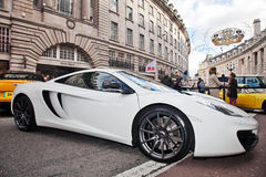 McLaren MP4-12C in Regent Street. LONDON - NOVEMBER 3: A 2012 McLaren MP4-12C sits on static public display, watched over by event stewards at the Regent Street Royalty Free Stock Images