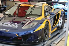 McLaren race car. McLaren 12C GT3 gets worked on in the garage area at the professional motorsports racing event, International Motor Sports Association, Sports Royalty Free Stock Image