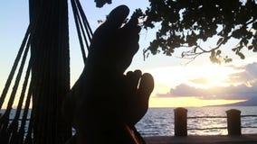 MCU dei piedi del ` s della persona che allungano e che si contorcono in un'amaca del mare durante il sunse video d archivio