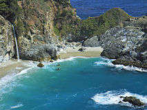 Mcway falls at Julia Pfeiffer Burns SP. Beautiful waterfall pouring onto beach in blue ocean cove stock photography
