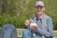 Mężczyzna łasowania jogurt outdoors Obraz Royalty Free