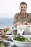 Mężczyzna łasowania posiłek Blisko morza Zdjęcia Royalty Free