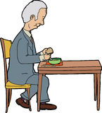 Mężczyzna łasowanie przy stołem Obraz Stock