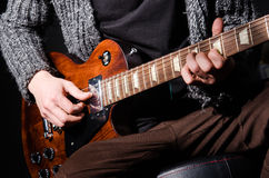Mężczyzna bawić się gitarę w ciemnym pokoju Obrazy Royalty Free