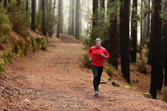 Mężczyzna bieg w lasowy drewien trenować Zdjęcia Royalty Free