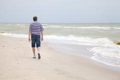 Mężczyzna chodzi na dennej plaży Zdjęcia Royalty Free