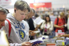 Mężczyzna czyta książkę przy książkową sprzedażą Obraz Royalty Free