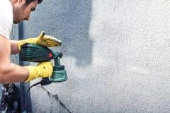 Mężczyzna maluje popielatą ścianę, odnawi zewnętrzne ściany nowy dom Zdjęcia Royalty Free