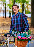 Mężczyzna na rowerze z kwiatami koszykowymi w parku Fotografia Royalty Free