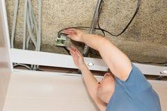 Mężczyzna naprawia elektrycznego drutowanie na suficie Fotografia Stock