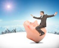 Mężczyzna obsiadanie na różowym prosiątko banku Zdjęcie Stock