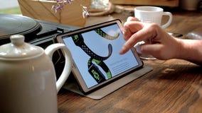 Mężczyzna odwiedza iWatch stronę internetową na pastylka komputerze osobistym w kawiarni zbiory wideo