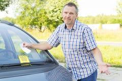 Mężczyzna patrzeje na mandat za złe parkowanie Obrazy Stock