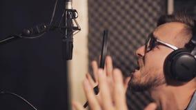 Mężczyzna śpiewa przy studiiem nagrań z hełmofonami zdjęcie wideo