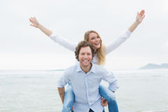 Mężczyzna piggybacking kobiety przy plażą Obrazy Royalty Free