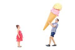 Mężczyzna przynosi ogromnego lody z podnieceniem dziewczyna Zdjęcia Royalty Free