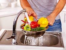 Mężczyzna płuczkowa owoc przy kuchnią. Zdjęcie Royalty Free