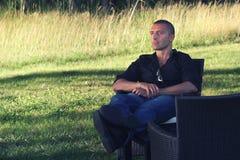 Mężczyzna relaksujący obsiadanie w naturze pojęcia ręki kieszeni relaksu zegarka nadgarstek Zdjęcie Stock