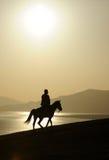 Mężczyzna ridig koń przy wschodem słońca Obrazy Stock