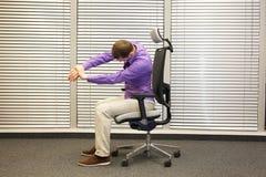 Mężczyzna rozciągania ręki, ćwiczy na krześle Zdjęcia Stock