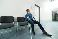 Mężczyzna siedzi na krześle z szczudłami Zdjęcia Stock