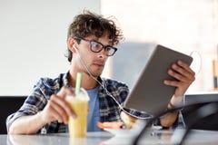 Mężczyzna siedzi przy kawiarnią z pastylka komputerem osobistym i słuchawki Fotografia Royalty Free