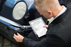 Mężczyzna trzyma cyfrową pastylkę egzamininuje uszkadzającego samochód Obraz Royalty Free