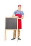 Mężczyzna w fartuch pozyci za blackboard Obrazy Royalty Free