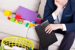 Mężczyzna w kostiumu obsiadaniu na kanapie Fotografia Stock