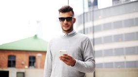 Mężczyzna w okularach przeciwsłonecznych z smartphone na miasto ulicie zbiory wideo