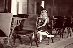 Mädchen am antiken Schuleschreibtisch Lizenzfreies Stockfoto