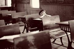 Mädchen am antiken Schuleschreibtisch Stockfotografie