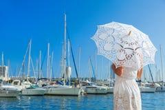 Mädchen auf dem Pier mit einem Spitzeregenschirm, der die Yacht betrachtet Lizenzfreie Stockfotos