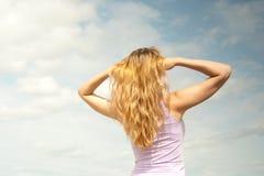 Mädchen auf einem Hintergrund des Himmels Stockbilder