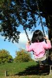 Mädchen auf einem Schwingen Stockbilder