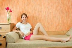 Mädchen auf Sofa Stockbilder